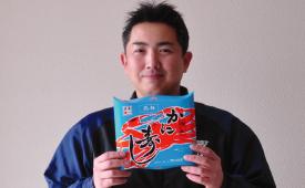 スタッフが「かに寿司」を持っている笑顔の画像